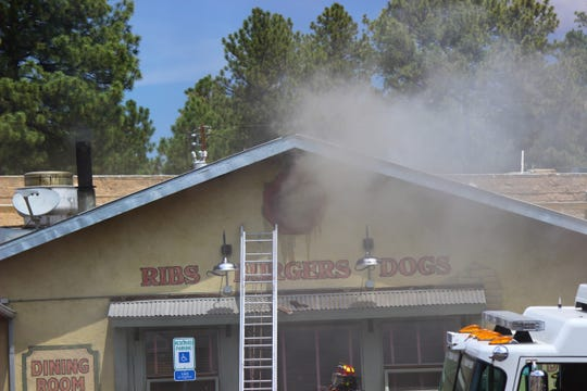 Smoke pours out an attic vent at Farley's Restaurant on Mechem Drive on Wednesday August 8 during a fire.