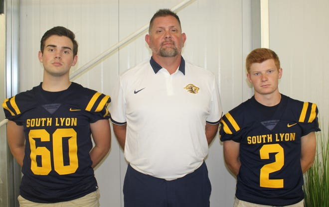 South Lyon head coach JeffHenson is flanked by seniors David Rende (left) and Michael Dancer.