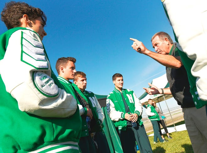 Novi boys cross country coach Robert Smith, gives a pep talk to Scott McPherson, Gabriel Mudel, and John and Aric Landy during his final season.