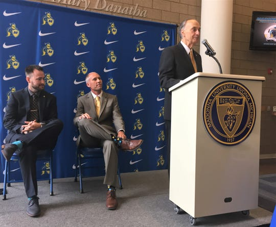 Madonna University President Dr. Michael Grandillo (right) addresses the crowd to announce the sport of football to its athletics program along with  sports information director Zachary Shore and athletic director Scott Kennell.
