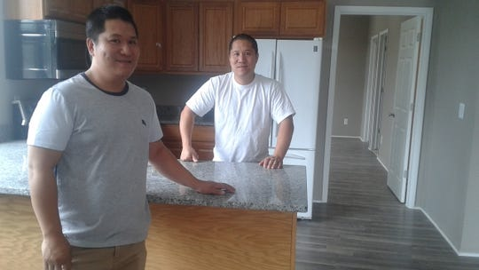 Danny Xie (left) and his brother, Sky Xie, show one of the residential units that will be available for rent above the Samurai Hibachi & Sushi restaurant in Farmington.