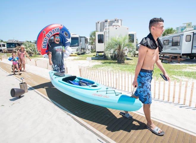 The Zevallos family, from Dallas, Texas, make their way to the water with their beach gear at the Pensacola Beach RV Resort in Pensacola on Tuesday, August 7, 2018.