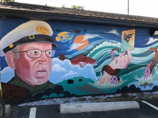"A mural at Palm Island Realty on Cervantes Street features a water scene, octopus tentacles, fish and an older man in a hat who represents ""Father Time."" The painting was by local artist Gabe Smith, with assistance from Jeremy Strength."