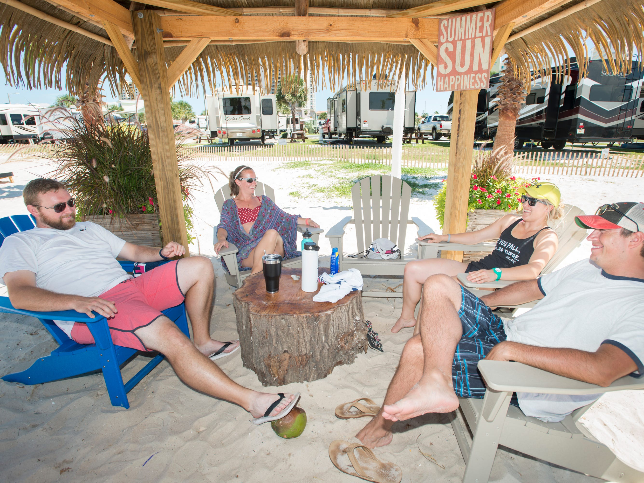 Pensacola Beach RV Resort residents Tyler and Katie Moos, left,  relax with their guests Tommy  Thrall, right, and Jordan Sjostrand, near the resort's Tiki Bar in Pensacola on Tuesday, August 7, 2018.