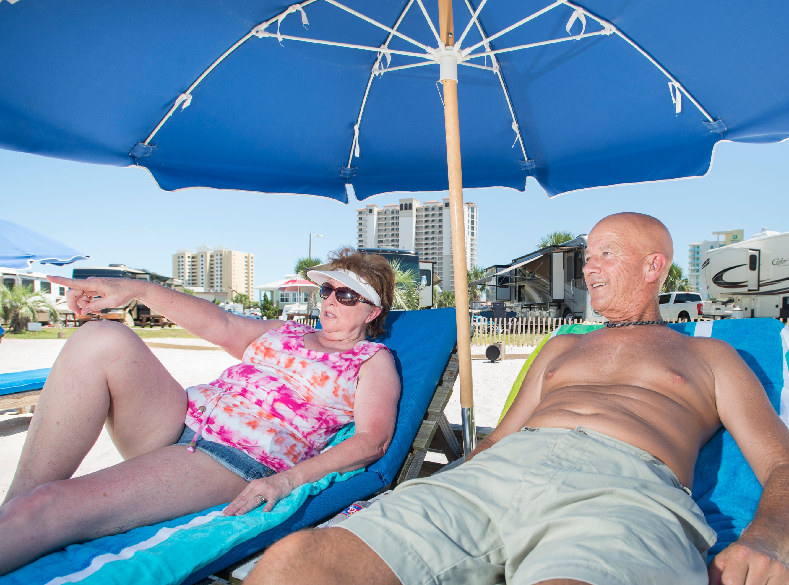 Darlene and Ted Wax, of Prairrieville, Louisiana, sit in the shade an umbrella on the Pensacola Beach RV Resort's beach in Pensacola on Tuesday, August 7, 2018.