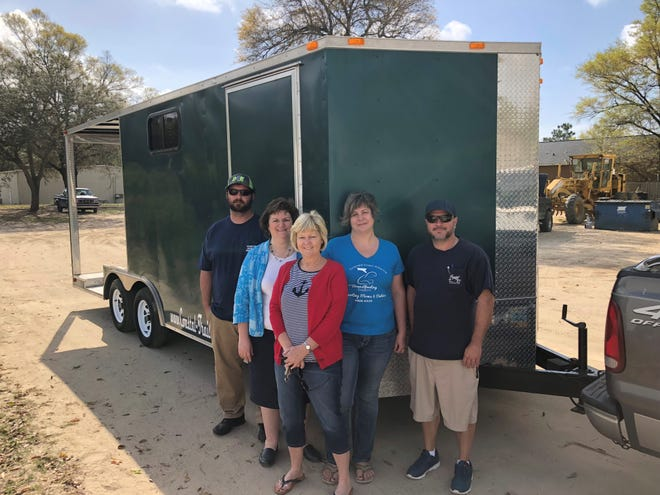 Coastal Trailers General Manager Adam Musick, left, and salesman Paul  McCrory, flank Emerald Coast Alliance for Breastfeeding Support officers, from left, president Ronda Yoder, treasurer Karen Shelton, and vice president Joy Weirick, in front of the nonprofit's newly acquired trailer for breastfeeding moms.