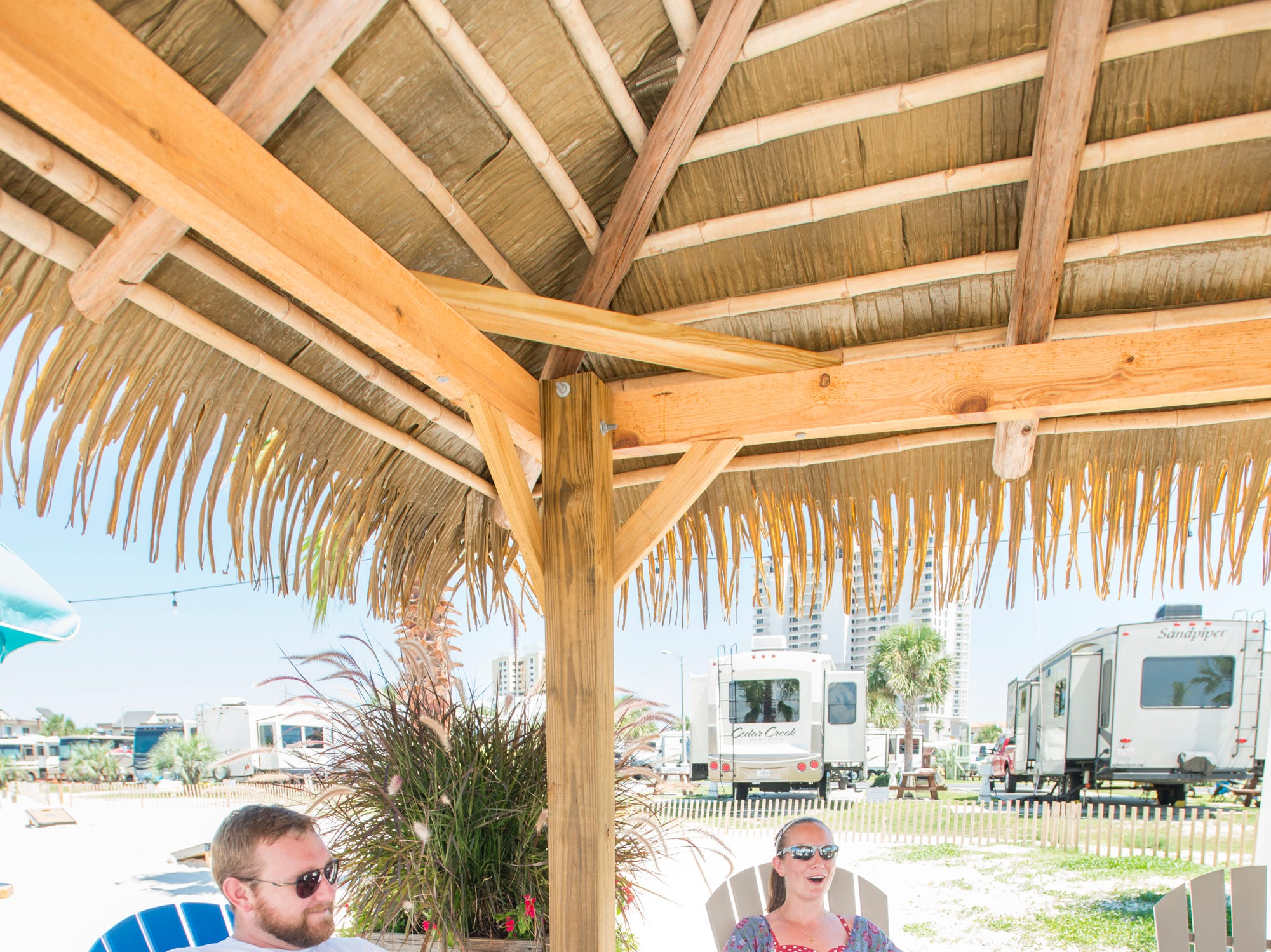 Pensacola Beach RV Resort residents Tyler and Katie Moos relax near the resort's Tiki Bar in Pensacola on Tuesday, August 7, 2018.