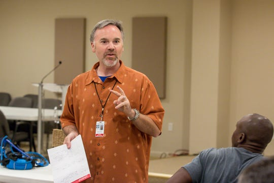 Director and co-founder Dan Signor goes over instructions with members of Pensacappella.