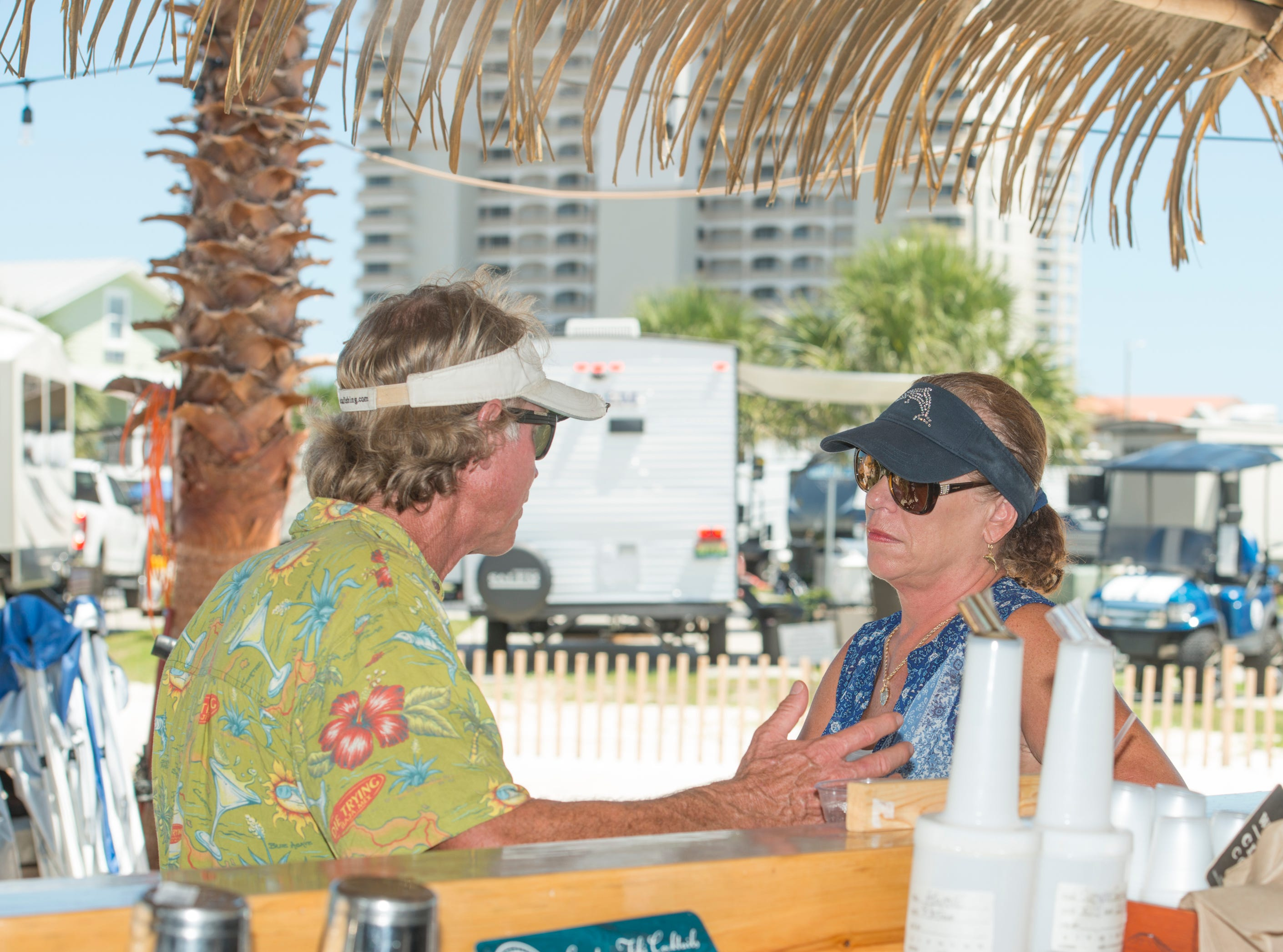 Pensacola residents Steve Moncreiff, left, and Cheryl Cooper chat while sitting at the Pensacola Beach RV Resort's Tiki Bar in Pensacola on Tuesday, August 7, 2018.