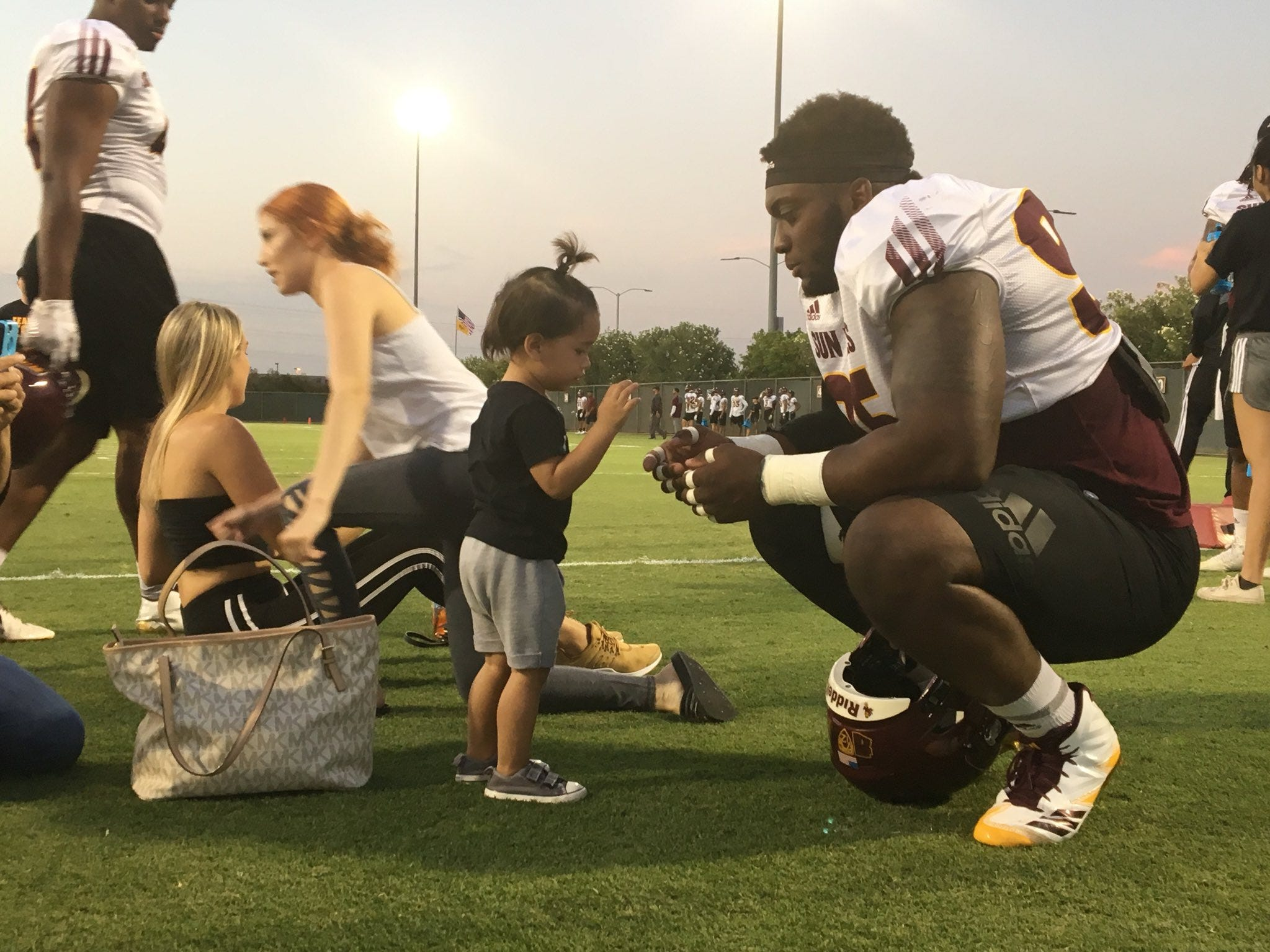ASU defensive lineman Renell Wren talks to a small ASU fan at practice on Aug. 7, 2018.