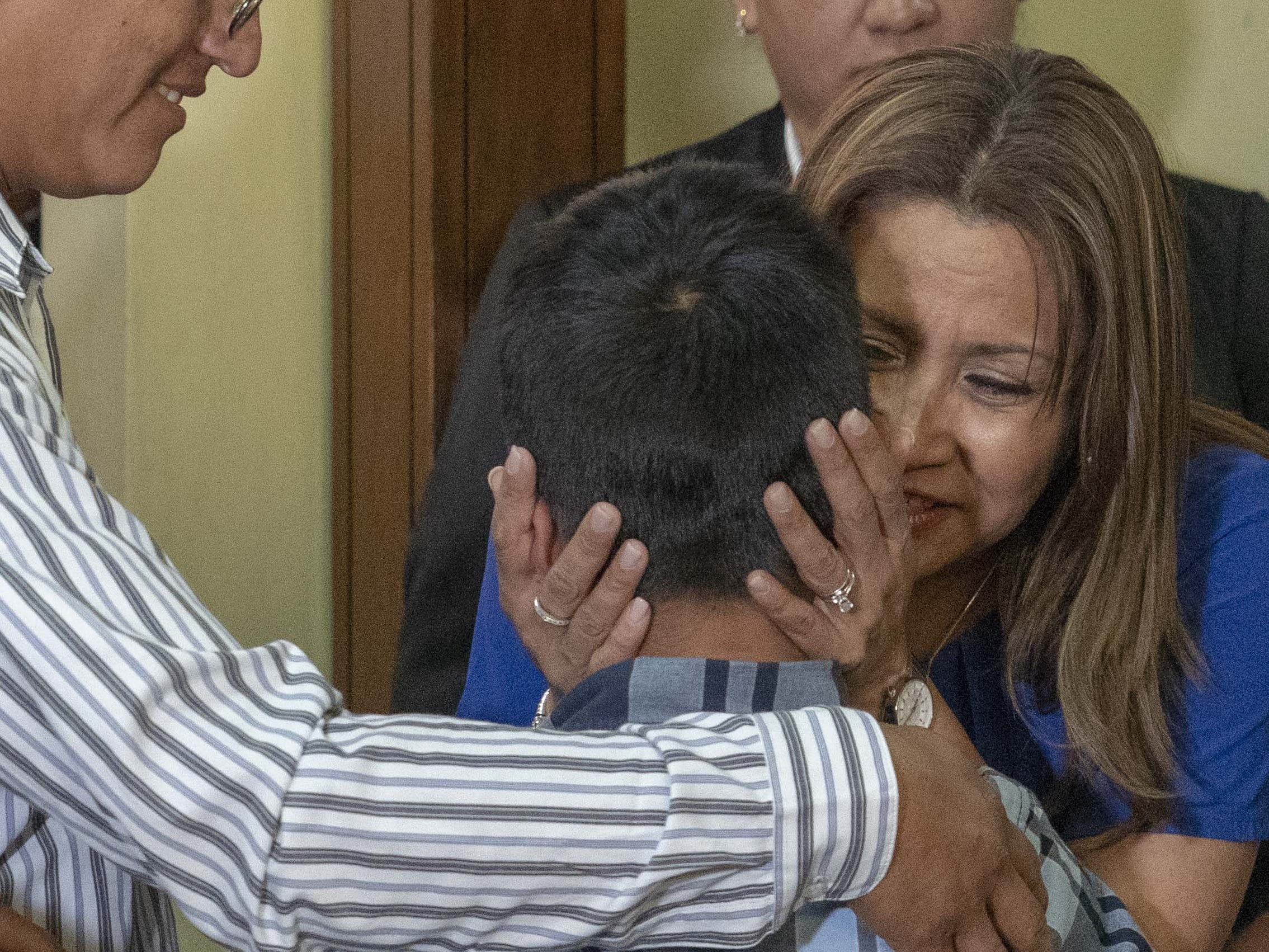 The First Lady of Guatemala, Patricia Marroquin (right) hugs a boy after he was deported and reunified with his father at the shelter in Guatemala on Aug. 7, 2018.