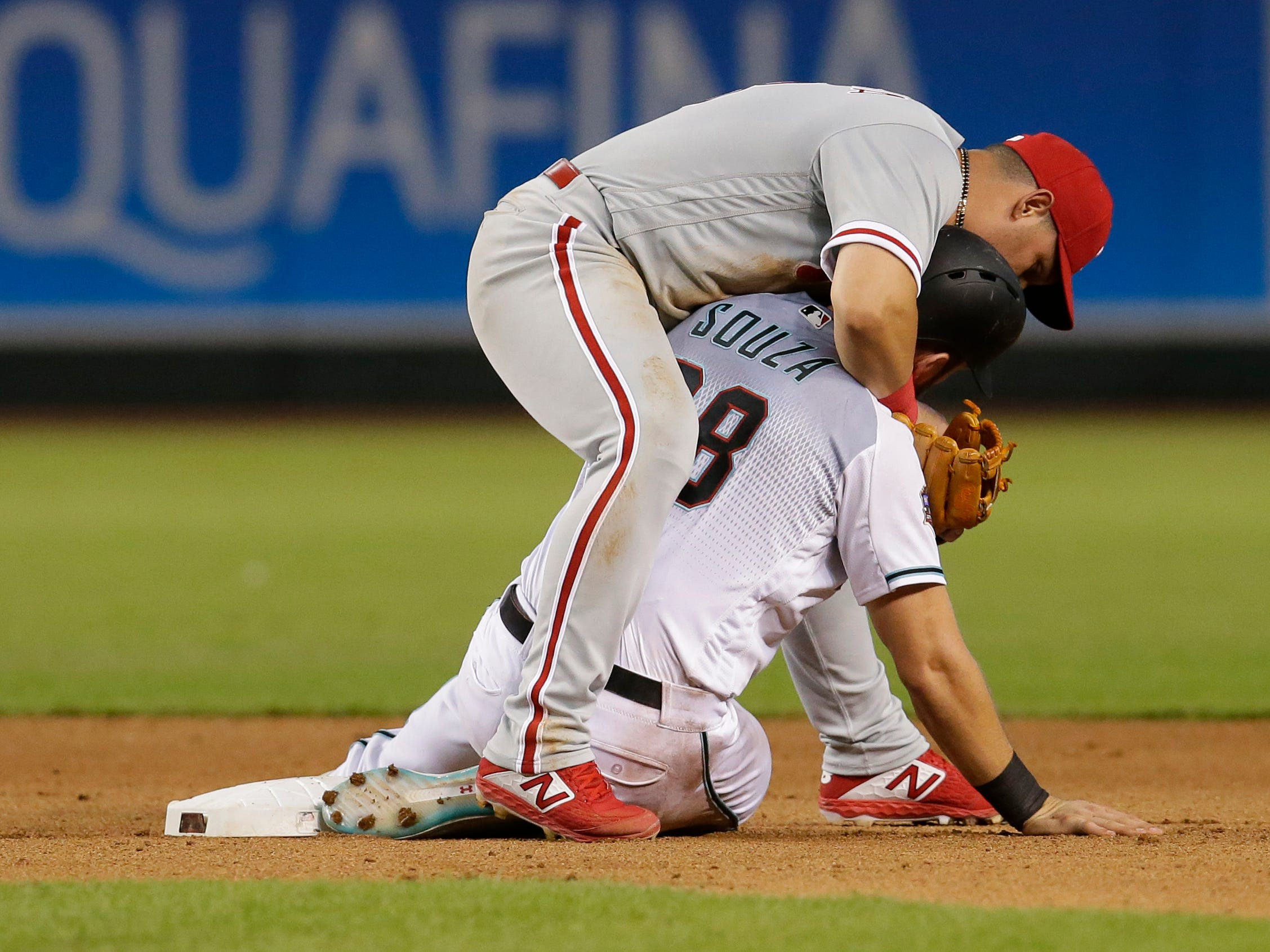 Philadelphia Phillies second baseman Asdrubal Cabrera (13) and Arizona Diamondbacks right fielder Steven Souza Jr. (28) in the eighth inning during a baseball game, Tuesday, Aug. 7, 2018, in Phoenix.