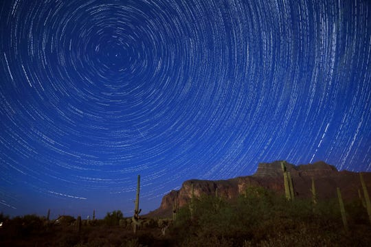 Star trails and a meteor from the Perseid Meteor Shower can be seen beyond the Superstition Mountains on Aug. 14, 2016, in Apache Junction.