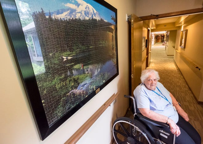 Sally Eagen, 93, is pictured next to a framed 3,000-piece puzzle she completed Wednesday, Aug. 8, 2018 at Lakeshore Woods. When the puzzle was completed, Eagen realized it was missing one piece, so she bought a second copy just to complete it.