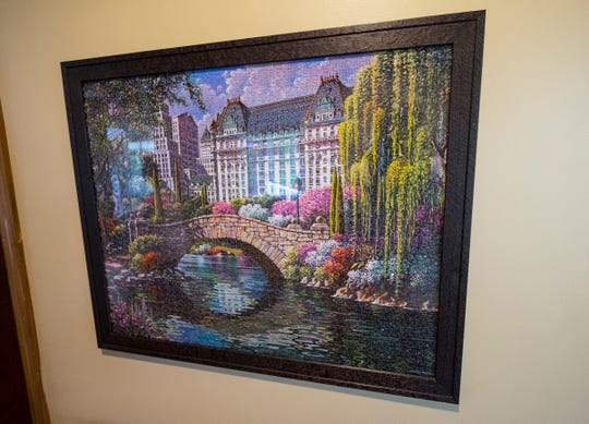A puzzle completed by Sally Eagen, 93, hangs in a frame in the hallways at Lakeshore Woods.
