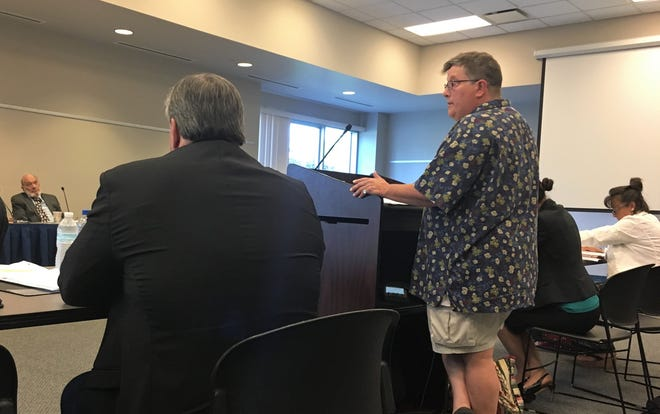 St. Clair County Community College sociology professor Heidi Browne speaks at the podium during a special meeting/hearing considering her dismissal on Aug. 7, 2018, in Port Huron.