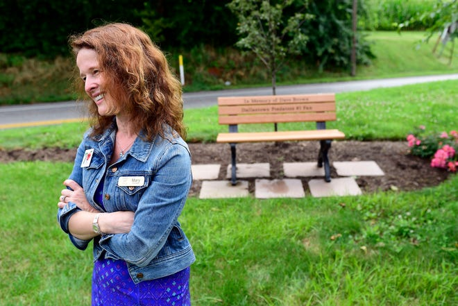 """Mary Brown, president of Brown's Orchards, stands in front of a bench, donated by her son's soccer team, the Dallastown Predators. The bench sits in front of Brown's Orchards in Loganville in memory of her husband, Dave Brown, the team's """"#1 fan,"""" who died in March 2018."""