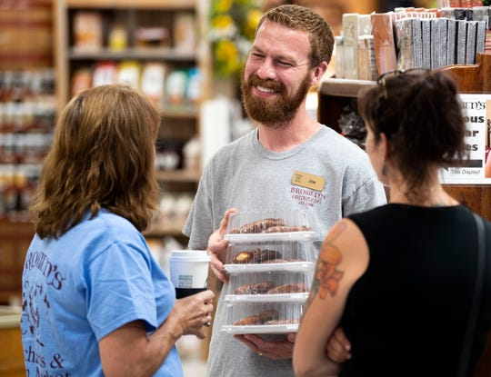Joe Doll, store manager at Brown's Orchards, interacts with customers in the store on Wednesday, August 1, 2018. Doll has been an employee at Brown's for 22 years. Doll has learned his work ethic from Stan Brown, who memorably said, 'If we have a little bit, we'll give a little bit.' Stan Brown died on August 12, 2017, at the age of 87.