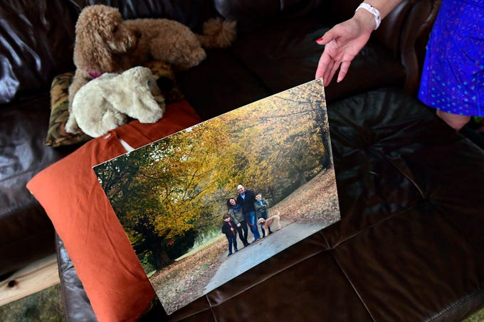 Mary Brown holds up the last family photo taken before Dave died. The photo was taken in the fall of 2017. Mary recalls the irony of traveling to Maryland to take photos on a farm when the family owns acres, but remembers how beautiful the foliage looked.