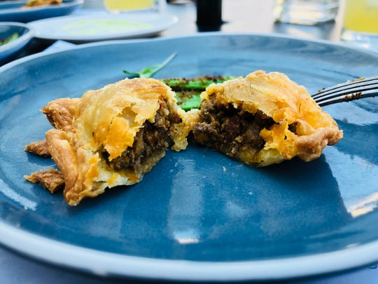The embanadas' filling is traditional, with a flaky crust and a side of Baja sauce.