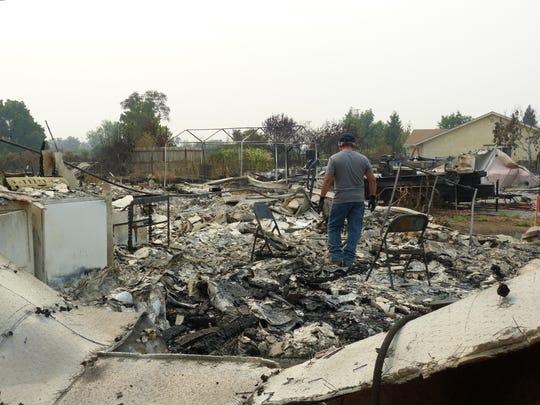 Van Kouang Saechao walks through the rubble of his Balboa Drive home.