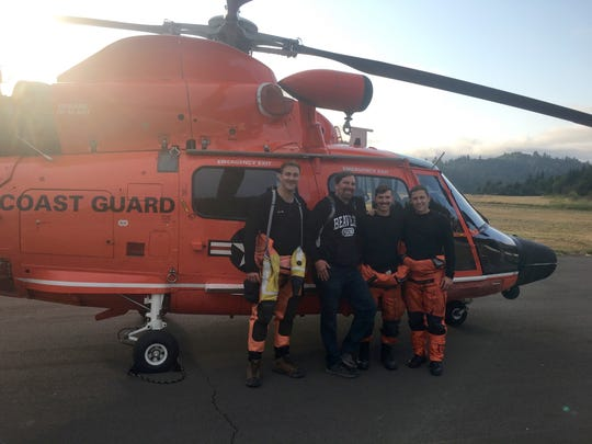 A man who fell near God's Thumb stands with the Coast Guard crew that  rescued him on Tuesday, August 7.