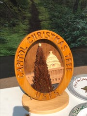 The wooden Capitol Christmas Tree plaque travels every year to the host national forest. All of the forests that have historically provided a tree are listed on the back of the plaque. Next year, the plaque will go to New Mexico's Carson National Forest.