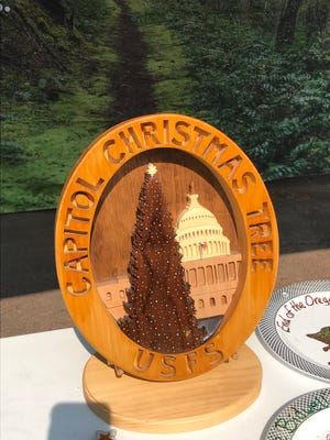 The wooden Capitol Christmas Tree plaque travels every year to the host national forest.