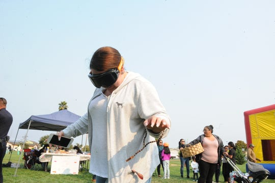 A girl tests out goggles that simulate visibility when intoxicated at the Laurel Heights National Night Out.