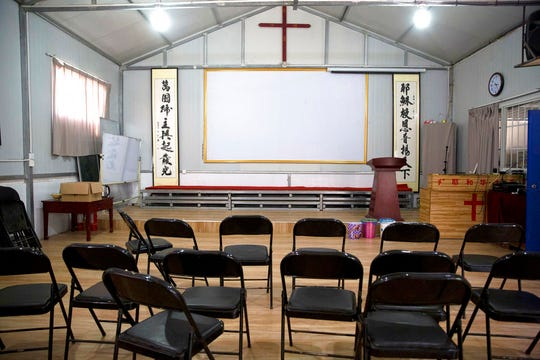 """In this photo taken Monday, June 4, 2018, Chinese calligraphy which reads """"All nations belong to the Lord arising to shine"""" at left and """"Jesus's salvation spreads to the whole world"""" at right are displayed below a crucifix in a house church shut down by authorities near the city of Nanyang in central China's Henan province. Under President Xi Jinping, China's most powerful leader since Mao Zedong, believers are seeing their freedoms shrink dramatically even as the country undergoes a religious revival. Experts and activists say that as he consolidates his power, Xi is waging the most severe systematic suppression of Christianity in the country since religious freedom was written into the Chinese constitution in 1982. (AP Photo/Ng Han Guan)"""