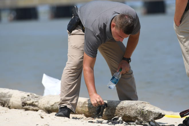 A police officer examines evidence on the beach at Homer Gudelsky Park in West Ocean City.
