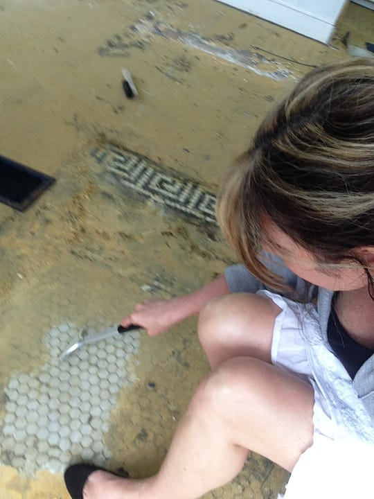 Julie Nash works to uncover the original tile floor in a former bank building in Parksley, Virginia. The building will house an art gallery once renovations are completed.