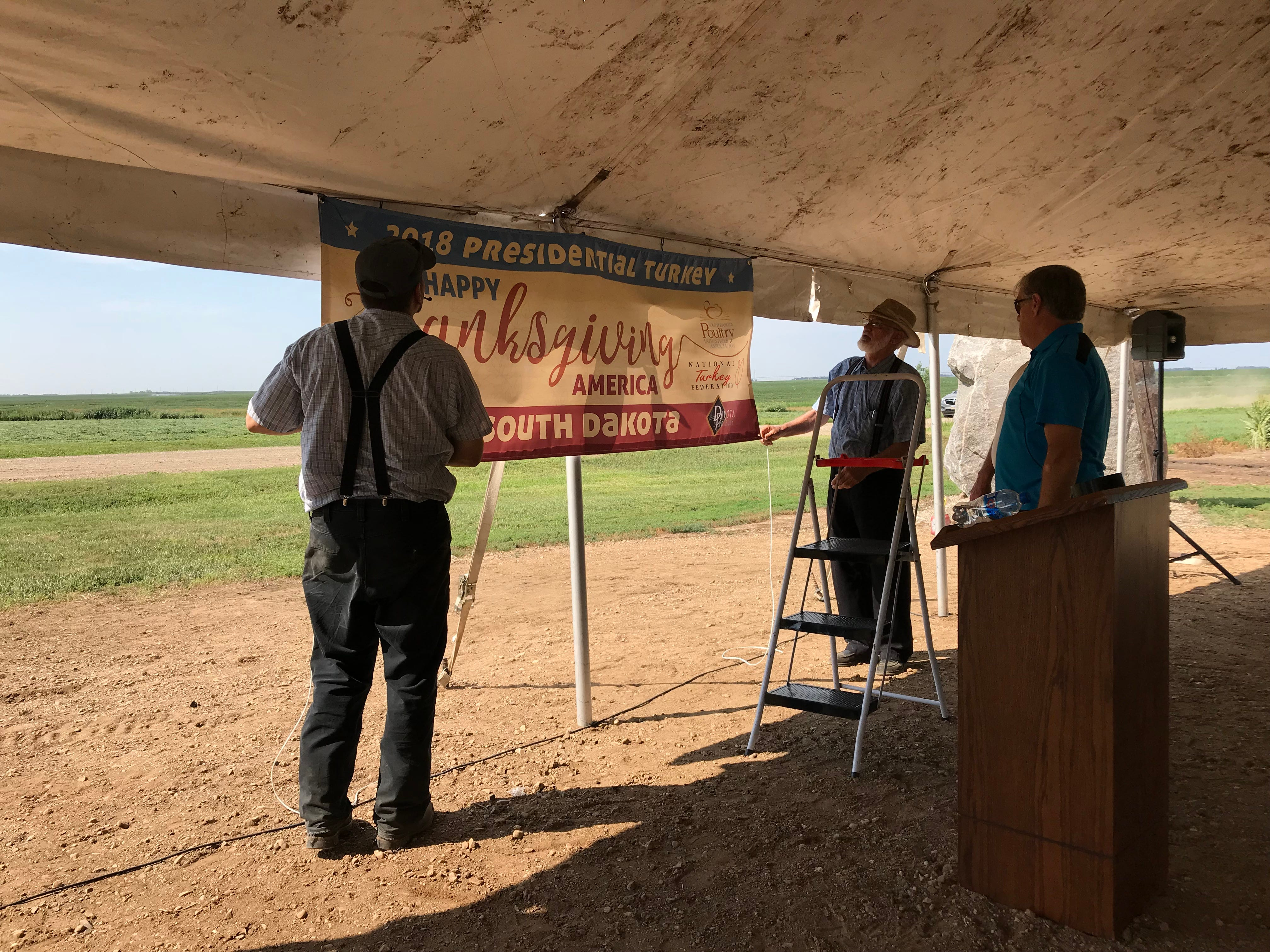 Organizers set up at a banner at the presentation of the turkeys selected as candidates for South Dakota's first National Thanksgiving Turkey, at the Riverside Turkey Farm outside Huron.
