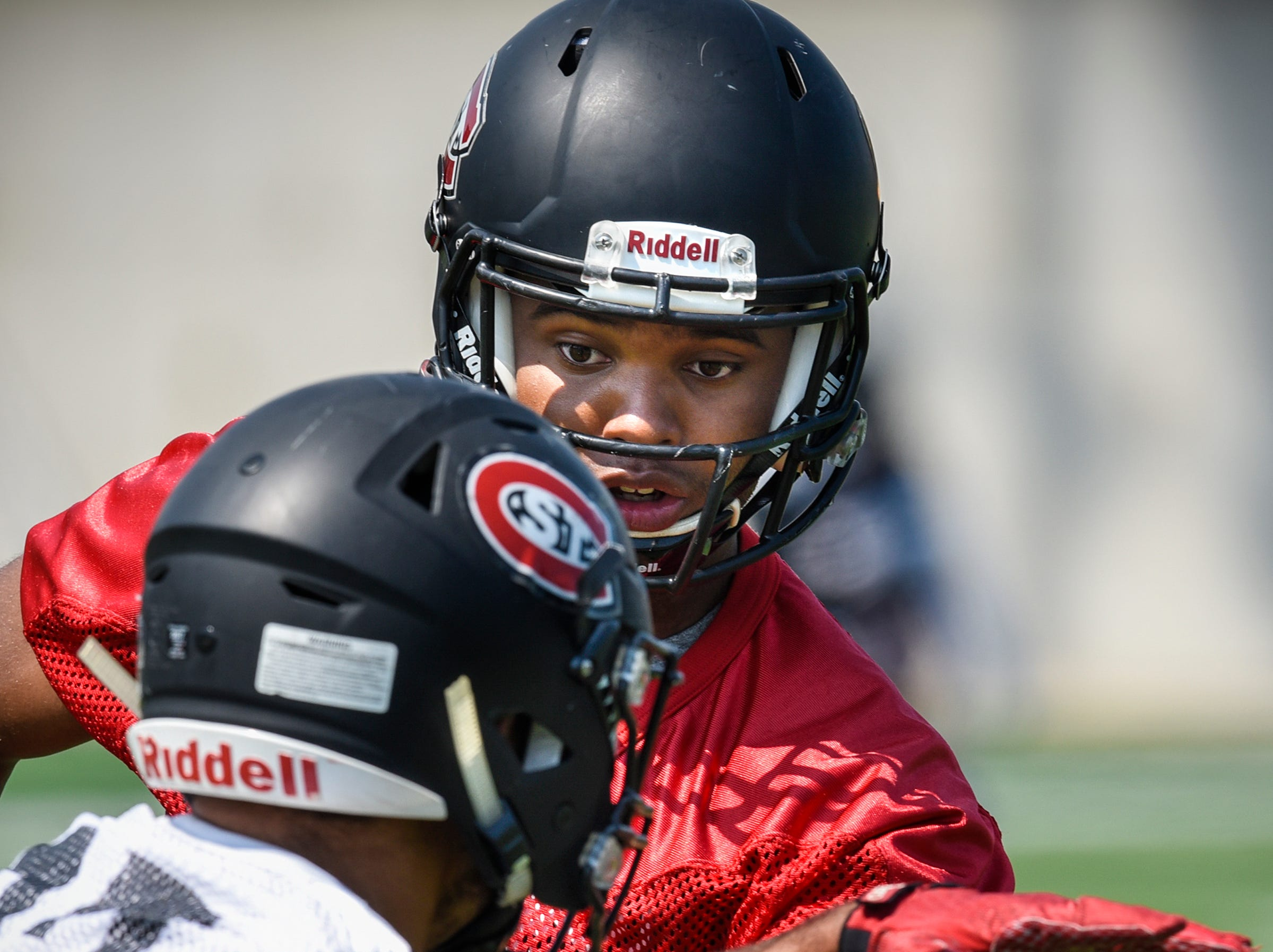 St. Cloud State University quarterback Dwayne Lawhorn hands off to a running back during practice Wednesday, Aug. 8, at Husky Stadium in St. Cloud.