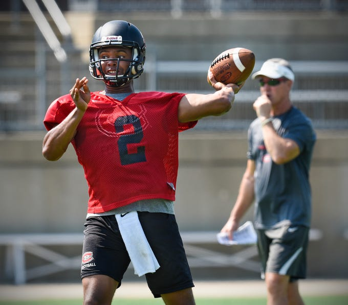 St. Cloud State University quarterback Dwayne Lawhorn throws a pass as head coach Scott Underwood observes during practice Wednesday, Aug. 8, at Husky Stadium in St. Cloud.
