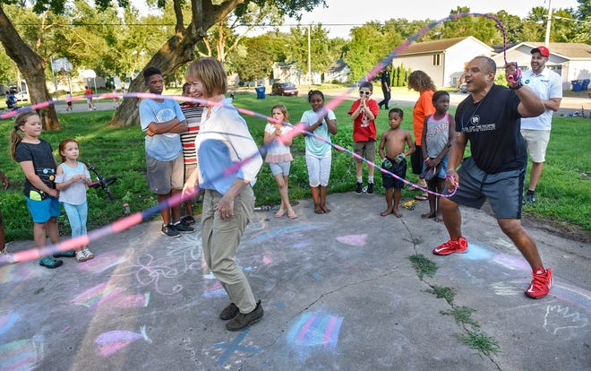 U.S. Sen. Tina Smith takes her turn in a game of Double Dutch as Jon Reese provides the power during National Night Out activities at Promise Neighborhood of Central Minnesota Tuesday, Aug. 7, in St. Cloud.
