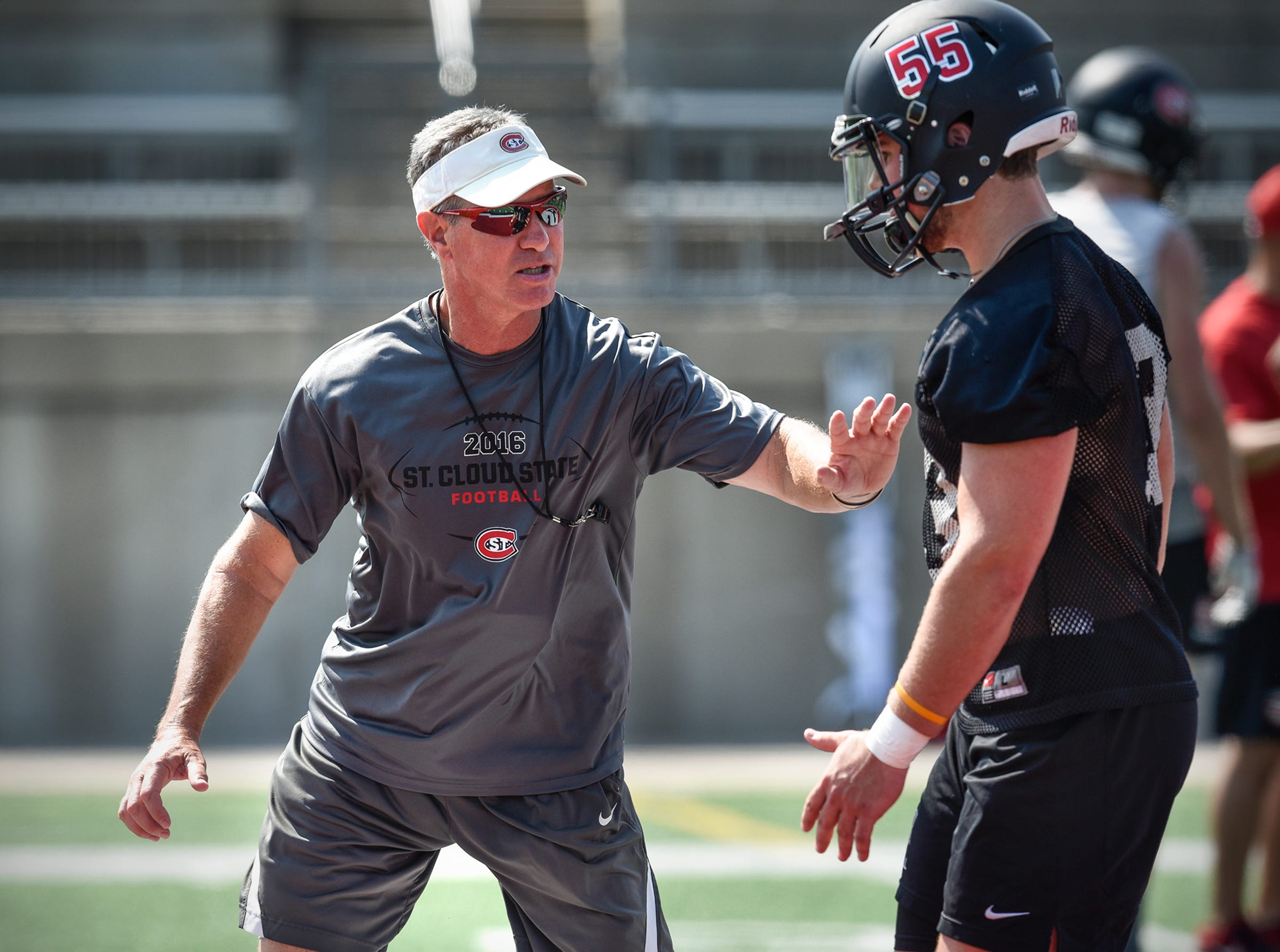 St. Cloud State head coach Scott Underwood talks with a player during practice Wednesday, Aug. 8, at Husky Stadium in St. Cloud.