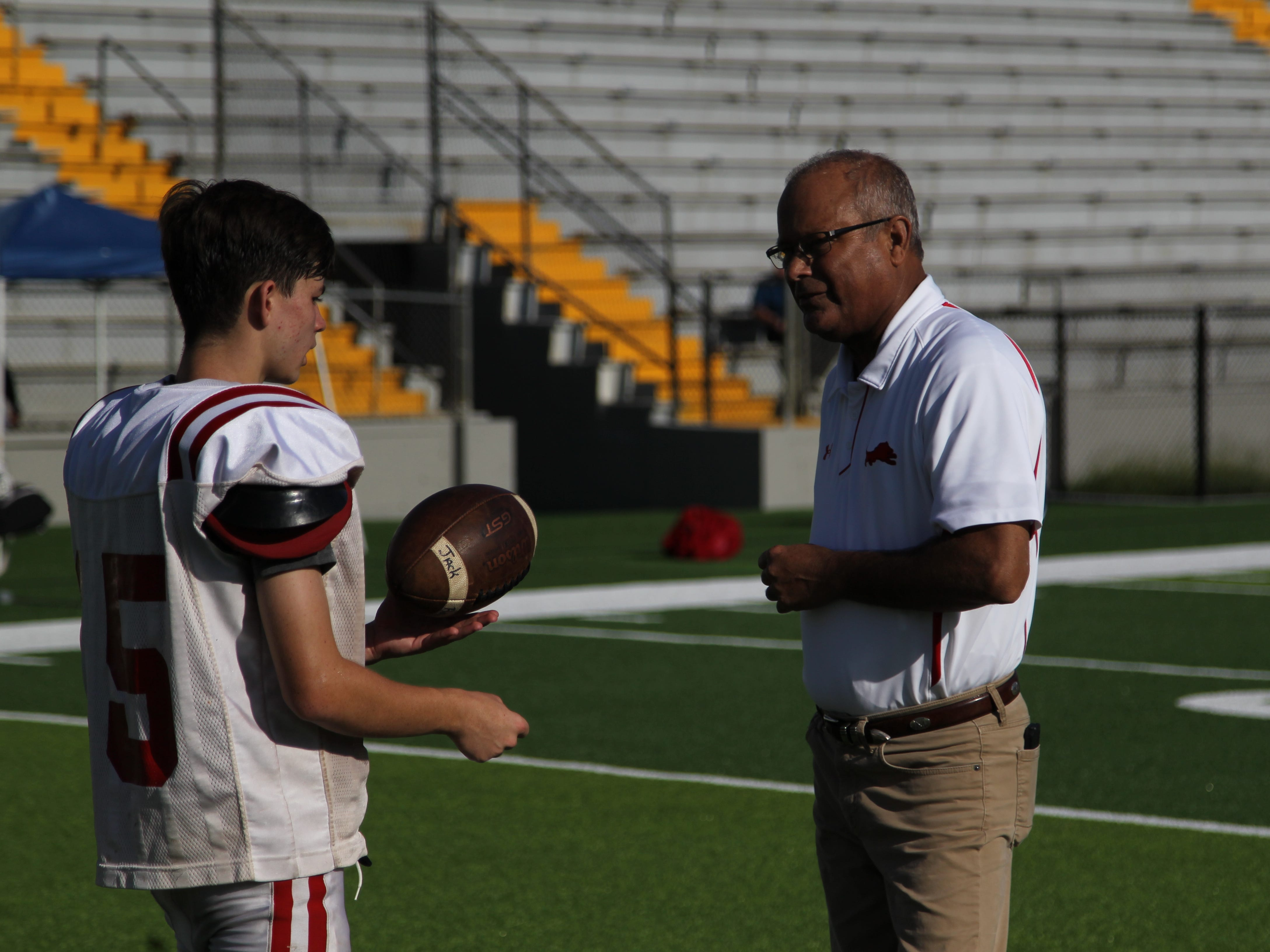 Leon athletic director Mark Feely works with a punter as Leon's football team practices at Gene Cox Stadium on its new turf field on Tuesday, Aug. 7, 2018. Formerly Capital Stadium, Cox Stadium was dedicated to legendary Leon coach Gene Cox in 1997.