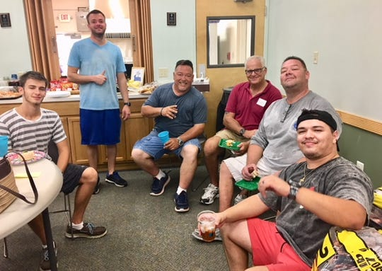 Vincent Rappa, left, Robert Noren, Robby Swain, Greg Scott, Keith Rappa and Logan Swain take a break from helping pack Family Meals bags.