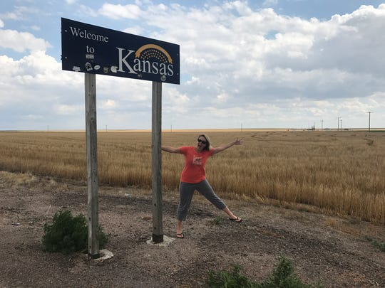 Laurie K. Blandford holds on to a Kansas welcome sign near the Colorado border during her July road trip driving across the country.