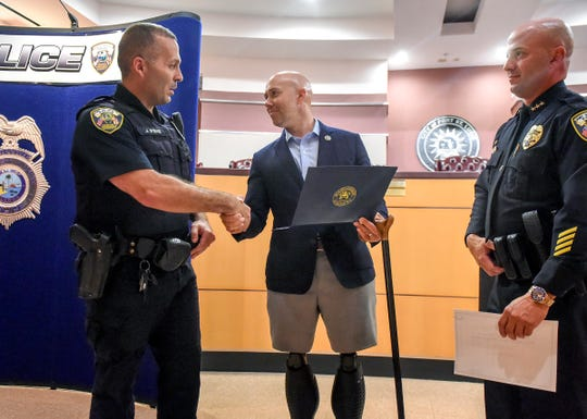 U.S. Congressman Brian Mast (middle) and Port St. Lucie Police Assistant Chief Richard DelToro (right) recognize the diligent work of Port St. Lucie Police Officer Joseph Byrne Wednesday, Aug. 8, 2018, for his part in an investigation into Edward Liroff during an award ceremony for Officer Byrne at the PSL City Hall. Liroff is accused of posing as a highly-decorated military veteran in his application for a job with the City of Port St. Lucie.