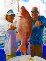 Safari 1 mate Jeff Wasenius, left, holds up a nice genuine red snapper for a customer last year. Red snapper in Atlantic waters can be kept July 12-14 and 19-20.