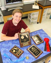 2018 Top Young Scientist finalist Zachary Hessler with some of his awards.
