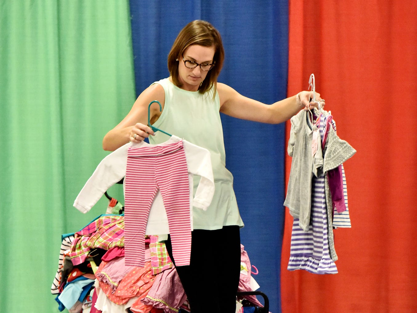 Ashley Wiggins separates clothes during the Switch-A-Roos children's consignment event at the TD Convention Center in Greenville on Wednesday afternoon, August 8, 2018.
