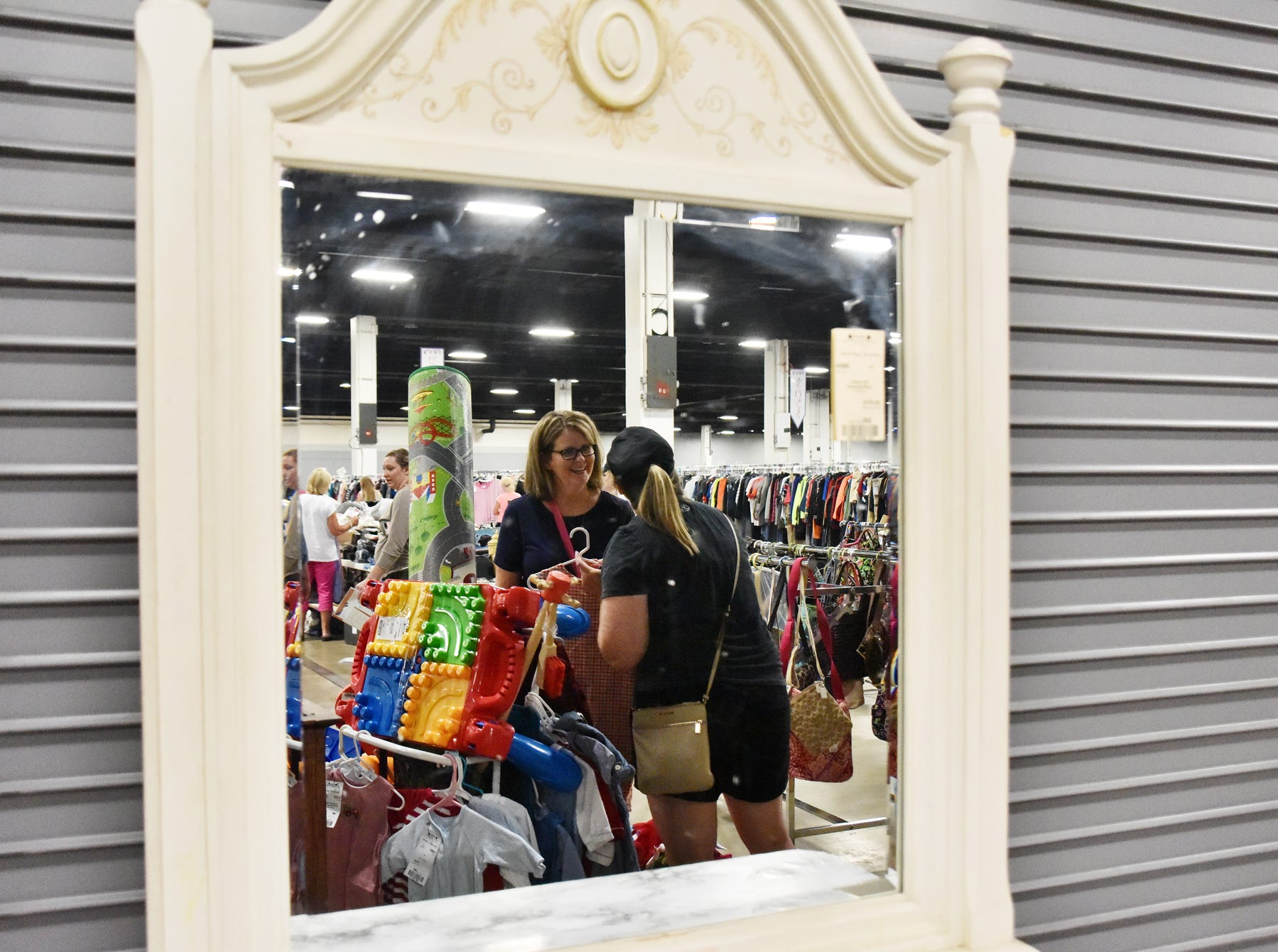 Diane Aiken, left, Jennifer McAlister are reflected in a mirror while shopping during the Switch-A-Roos children's consignment event at the TD Convention Center in Greenville on Wednesday afternoon, August 8, 2018.