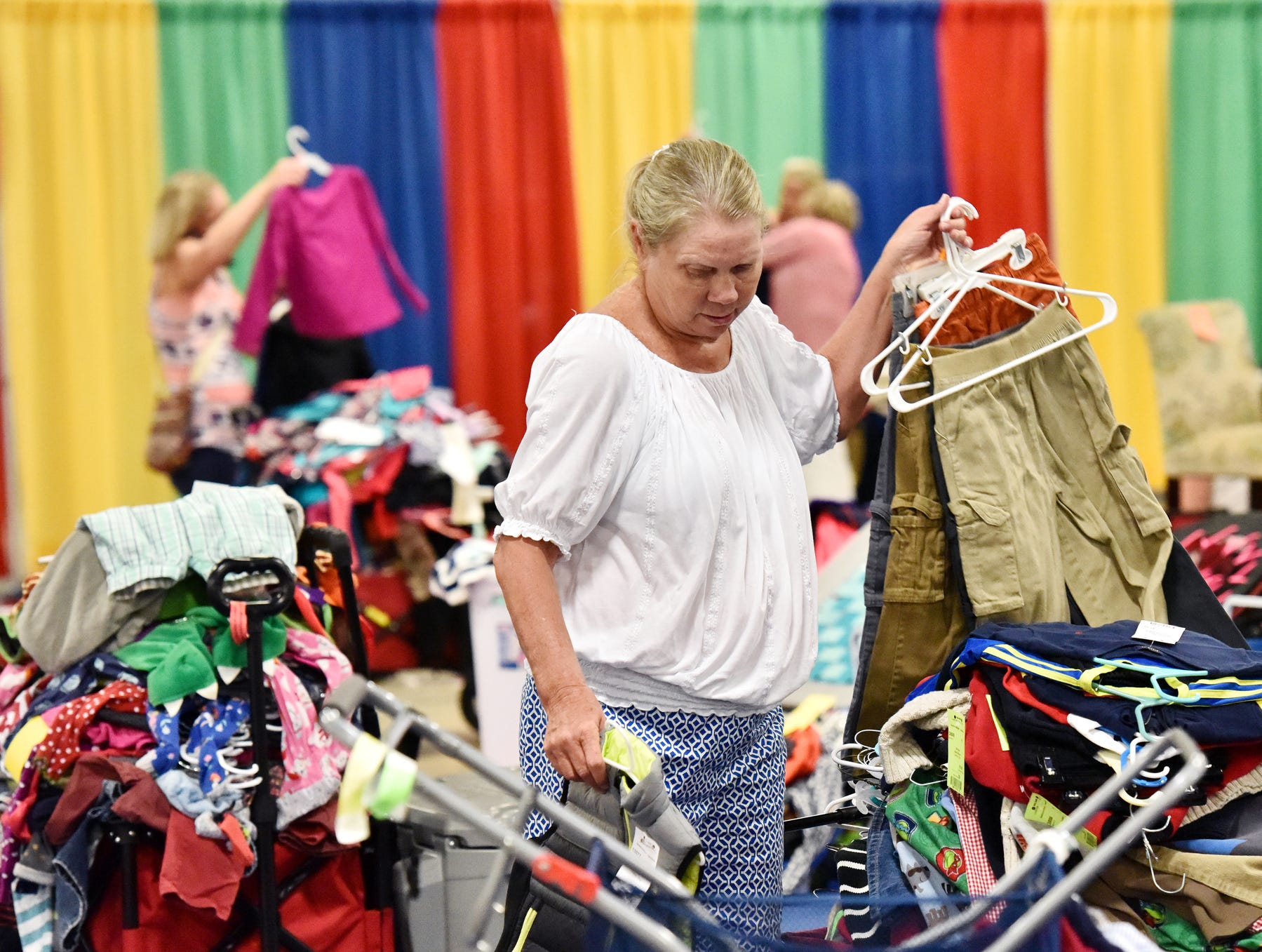 Monecca Chadwell sorths clothing during the Switch-A-Roos children's consignment event at the TD Convention Center in Greenville on Wednesday afternoon, August 8, 2018.