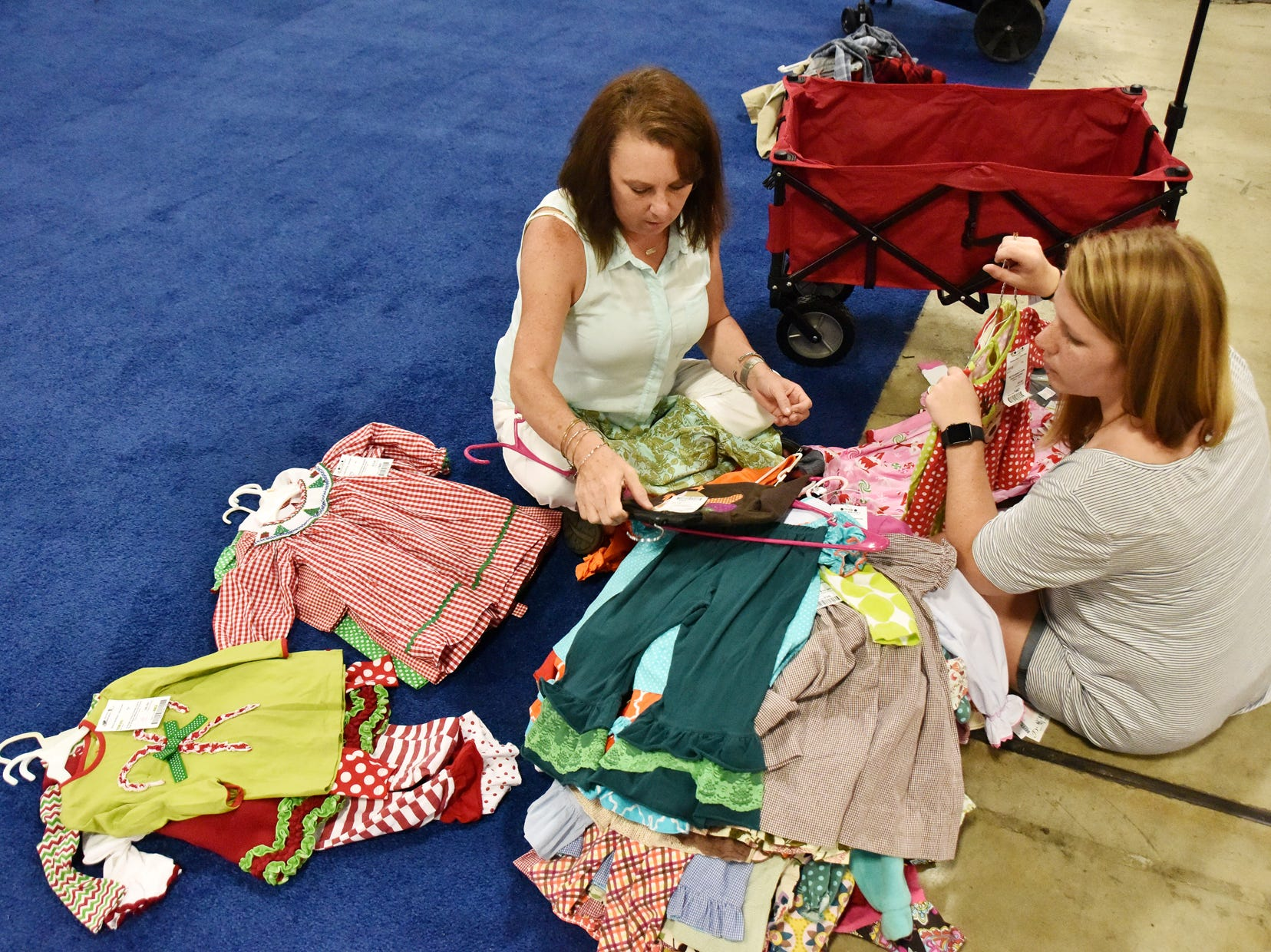 Chelsea Roberts, right, and Rebecca Jones sort clothes during the Switch-A-Roos children's consignment event at the TD Convention Center in Greenville on Wednesday afternoon, August 8, 2018.