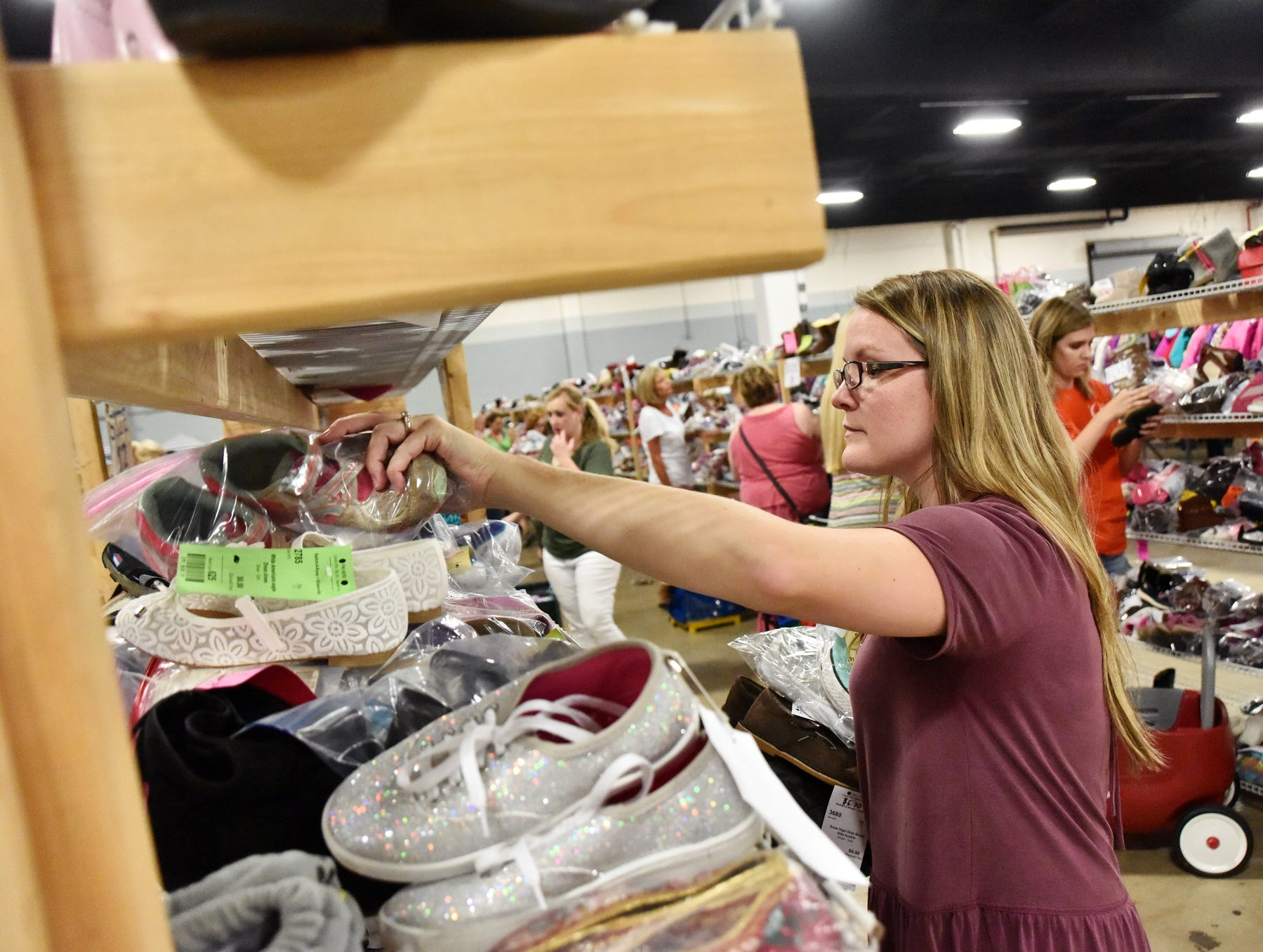 Megan Grigg sifts through a shelf of shoes during the Switch-A-Roos children's consignment event at the TD Convention Center in Greenville on Wednesday afternoon, August 8, 2018.