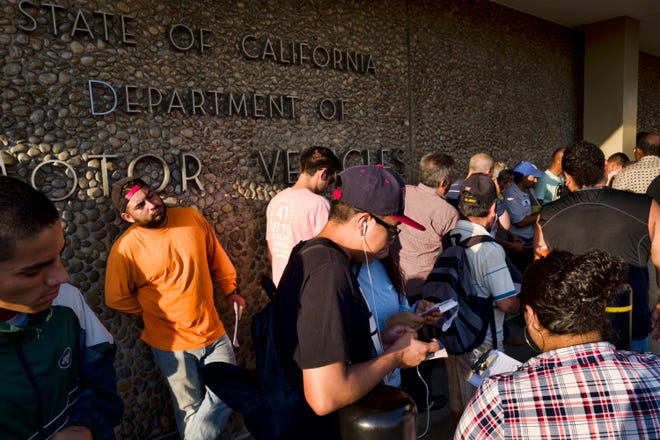 In this file photo from a few weeks ago, people line up at the California Department of Motor Vehicles prior to opening in Van Nuys.