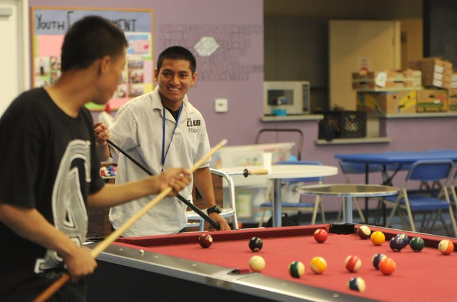 Staff member Juan Romero plays pool with a youth attending an evening reporting center at a Boys & Girls club in Oxnard in this photo shot in 2013.